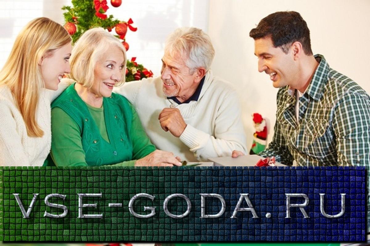 Glückliche Eltern beschenken Großeltern zu Weihnachten im Wohnzimmer